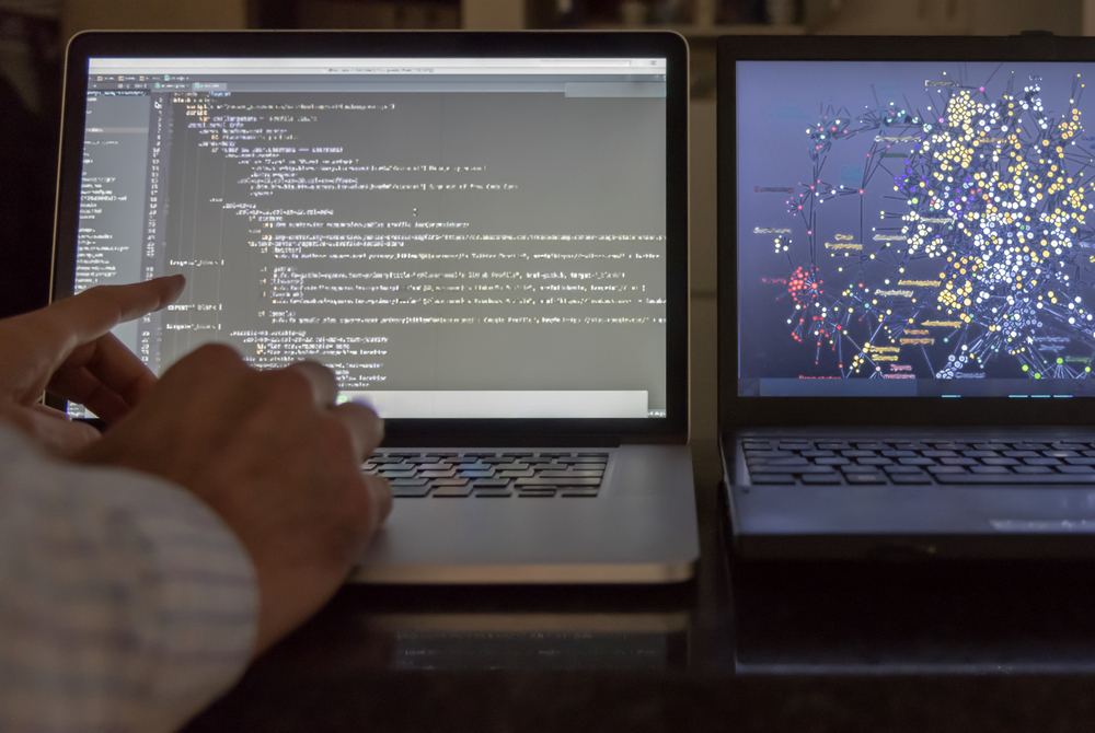 Computer,Scientist,Pointing,At,Code,Screen,With,Algorithmic,Data