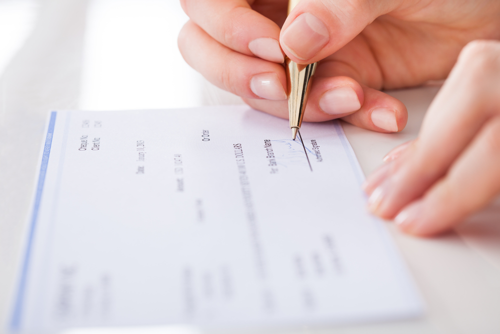 Cropped,Image,Of,Businesswoman,Signing,Cheque,At,Desk